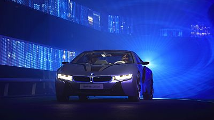"""Blue laser light forms a """"birthing tunnel"""" that highlights a BMW high-efficiency """"i"""" series car"""