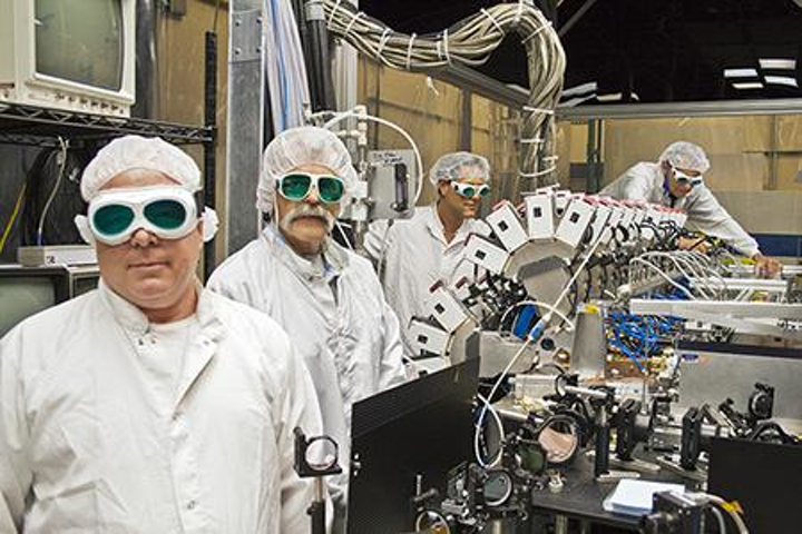 The Boeing Thin Disk Laser system, which integrates a series of high-power industrial lasers to generate one concentrated, high-energy beam, exceeded required thresholds for power and beam quality during a demonstration for the Department of Defense's Robust Electric Laser Initiative (RELI) effort. In this photo, Boeing Thin Disk Laser engineers work with the system's main optical bench. (Image credit: Boeing)