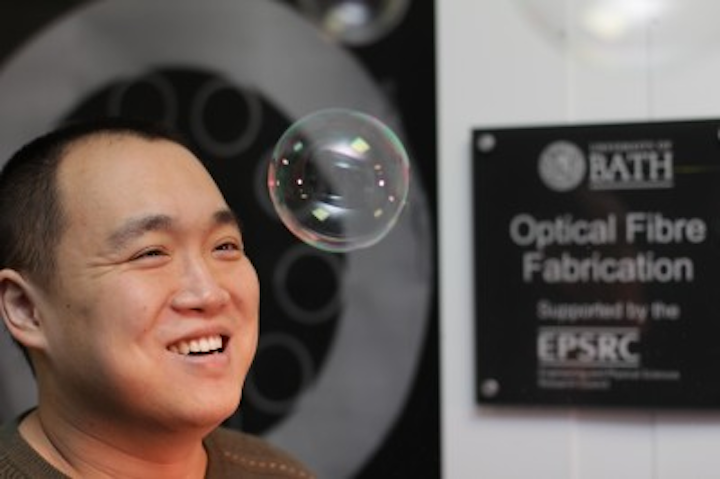 Fei Yu from the University of Bath helped develop the new hollow-core optical fiber that lases in the mid-infrared region. The long and thin bubbles of glass in the fiber reflect light into the fiber's core in a similar way to how light reflects off the surface of a soap bubble, making it appear iridescent. (Image credit: University of Bath)