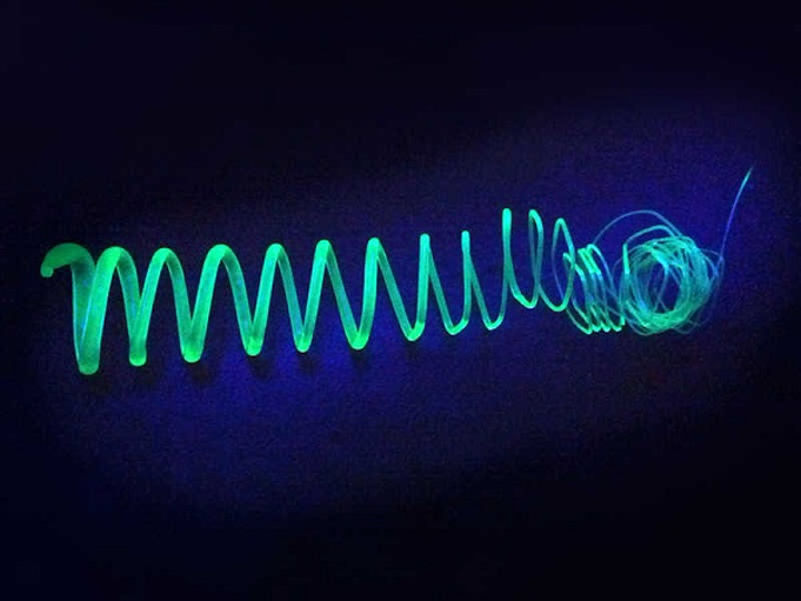 An extruded spiral made of polymer-coated silicon nanosheets glows in UV light. (Image credit: Tobias Helbich / TUM)