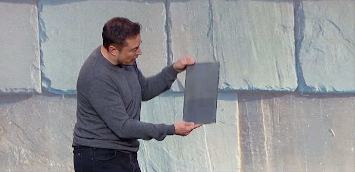 Tesla CEO Elon Musk is seen holding a tile amid an image of one style of the Tesla solar roof; note the solar panel just under the semi-transparent tile surface. (Image credit: Business Insider)