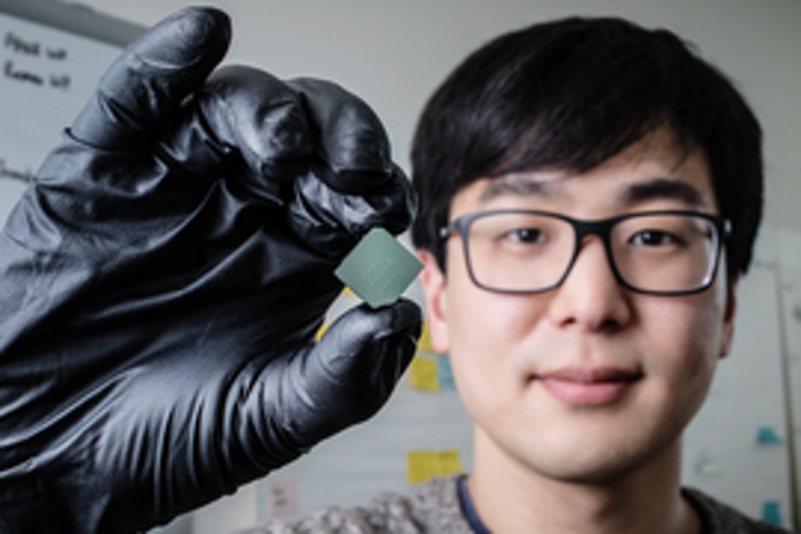 Mechanical science and engineering student and lead author of a new study Benjamin Sohn holds a device that uses sound waves to produce optical diodes tiny enough to fit onto a computer chip. (Image credit: University of Illinois at Urbana-Champaign)