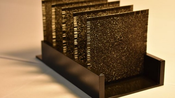 An artificial neural network, composed of a series of polymer layers, works using light that travels through it and artificial intelligence algorithms. Each layer is 8 cm square. (Image credit: Ozcan Research Group/UCLA)