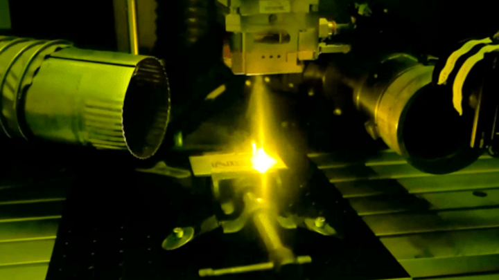 Inside NIST's laser welding booth, a high-power laser melts a piece of metal to form the letters NIST. (Image credit: Paul Williams/NIST)
